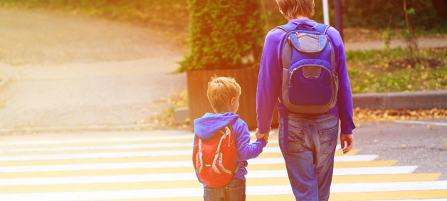 father and son wear backpacks at crosswalk