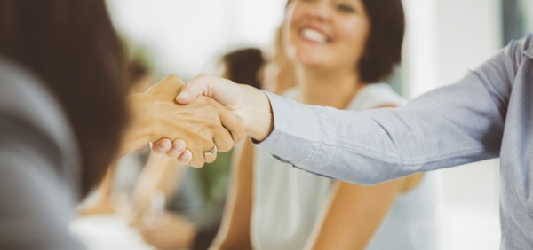 handshake in front of a smiling woman
