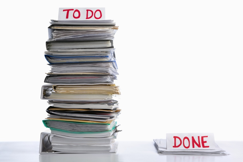large stack of do papers next to a small pile of done
