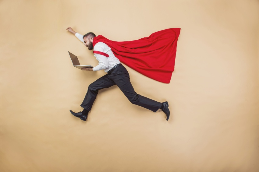 man wearing cape and holding a laptop