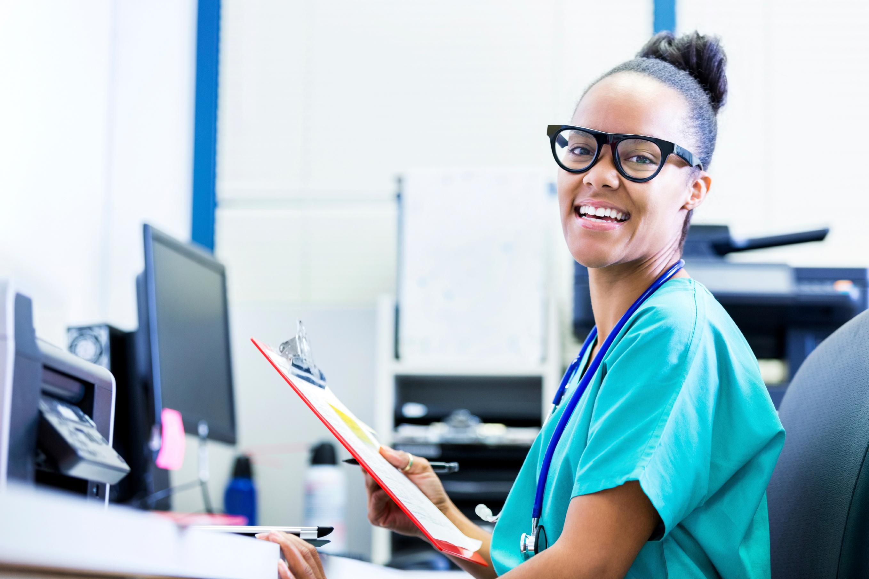 smiling nurse holding clipboard at computer desk