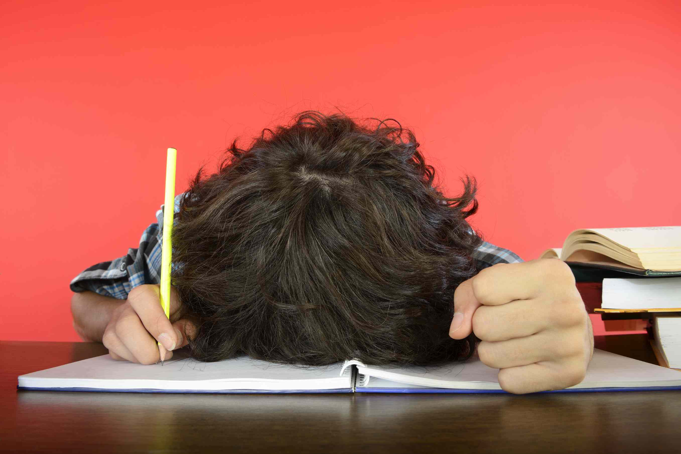 stressed student with head on notebook