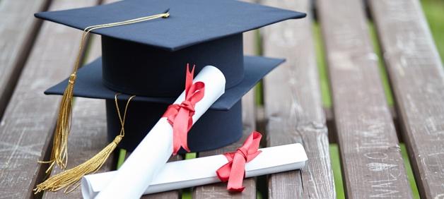 two graduation caps college degrees